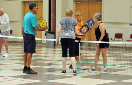 Photo example – four older adults talking at the pickleball net during a break
