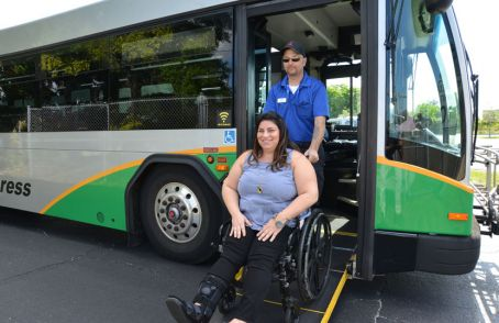 Photo example – a middle-aged woman in a wheelchair boarding the Sarasota County Area Transit (SCAT) bus with help from the bus driver
